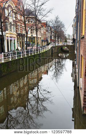 Canal and street with bicycle parking lot in Dutch Delft old city center