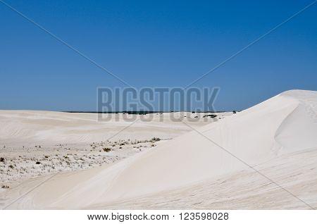 Stunning white desert landscape at the Lancelin Sand Dunes under a clear blue sky in Western Australia.