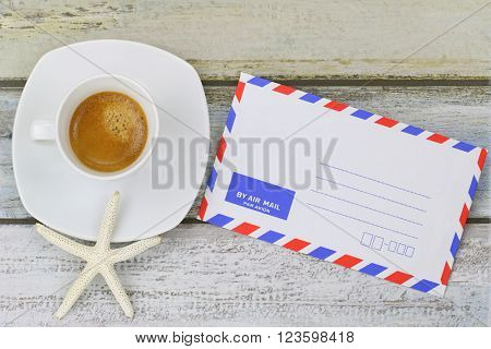Starfish on freshly brewed espresso coffee next to blank classic air mail envelope