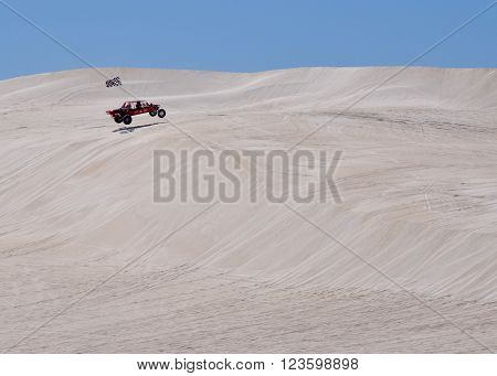 LANCELIN,WA,AUSTRALIA-SEPTEMBER 28,2015: Dune buggy recreational vehicle jumping the white sand dunes on a clear day in Lancelin, Western Australia.