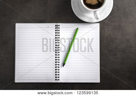 Notebook with pen and cup of coffee. Top view of writer's workplace