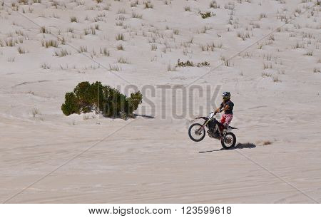 LANCELIN,WA,AUSTRALIA-SEPTEMBER 28,2015: Motorbike stunts at the white sand dunes in Lancelin, Western Australia.