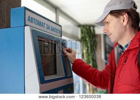 Man buying subway tickets using vending machine in Sofia, Bulgaria