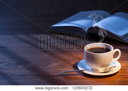 A cup of coffee, an open book on a desk.