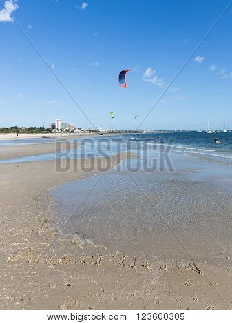 Australia inscription on the sand with shells on a large beautiful Australian beach and unrecognizable people go kite surfing and beautiful bright sails flying over blue sea Australia