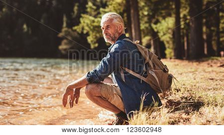 Senior Male Hiker Relaxing By A Lake And Admiring The View