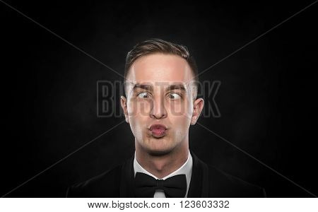 Portrait of a young cross-eyed businessman with funny face over dark background.