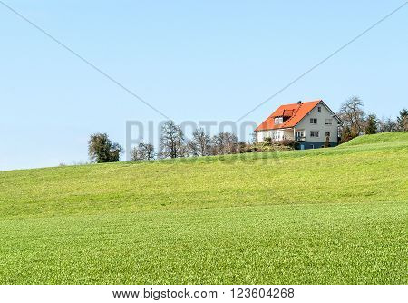 idyllic residential house surrounded by green pasture seen in Southern Germany at early spring time