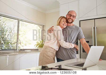 Loving Couple In Kitchen With A Laptop