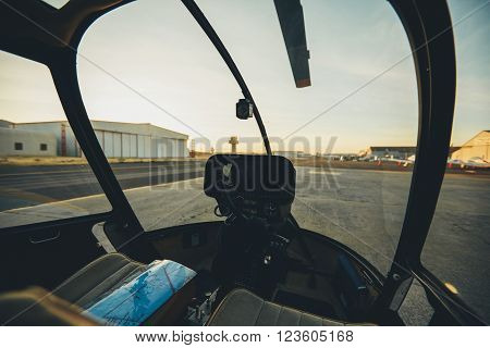 Inside view of a helicopter cockpit with instrument panel dashboard. Helicopter parked at airport.