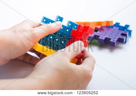 Hand on jigsaw puzzle game stock photo