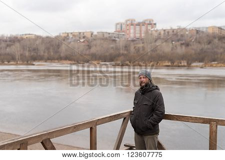 Bored man with a beard on a cityscape background