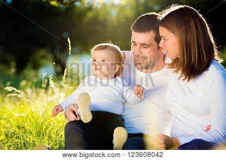 Mother and father holding their little son, sitting on the grass outside in green sunny nature