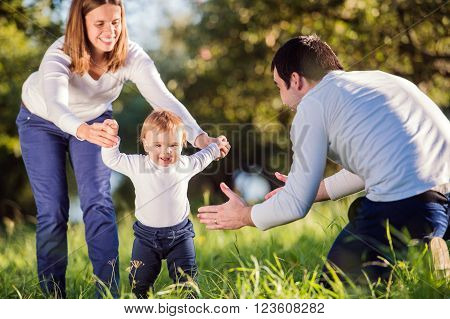 Mother and father holding their little son making first steps outside in green sunny nature