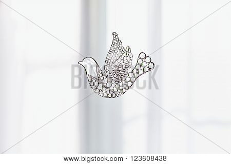 Souvenir glass dove, symbol of peace and spring. Figurine of a bird in flight Dove transparent. A beautiful sign of spring. With copy space. Glass toy on the background of a window