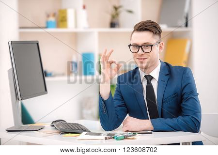 Young businessman with suit working in office. Businessman near computer showing ok sign. Office interior with bookcase