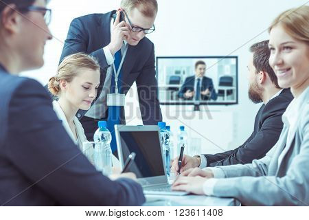 Business women and businessmen during video conference sitting in light interior