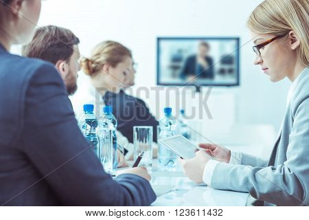 Elegant men and women sitting in light office having video conference