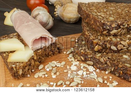 Ham, cheese and whole wheat bread. Freshly baked whole wheat bread. Preparing homemade breakfast. Various ingredients for the meal. Sliced bread on cutting board. Advertising on the bakery.