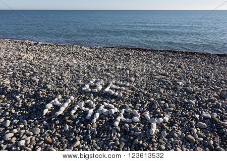 The Sign Be Happy Made From White Pebbles On Pebble Beach On The Sea