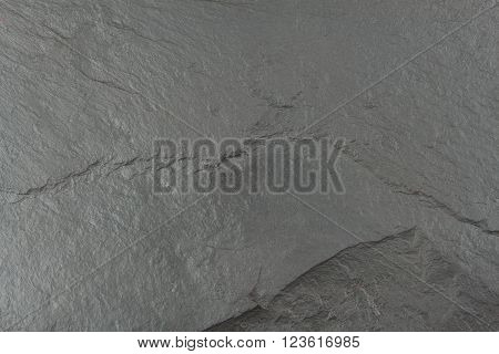 Dark black slate board. Texture chipped stone. Slate tile. Building material. Place for your text.