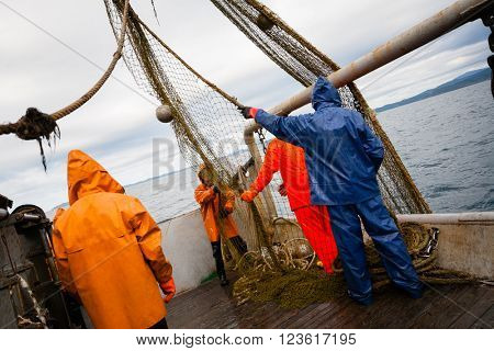 Fishermen in protective suits on deck Fishing vessel. Morning time.