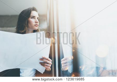 Portrait businesswoman wearing suit and holding papers in hands. Open space loft office. Panoramic windows background