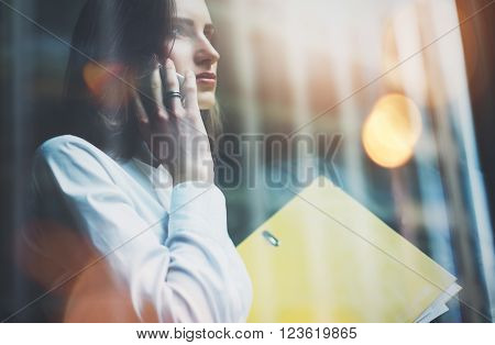 Photo woman wearing white shirt, talking smartphone and holding business files in hands. Open space loft office. Panoramic windows, night city background. Horizontal mockup, bokeh.