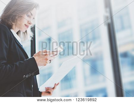 Pbusiness woman wearing suit, looking smartphone and holding documents in hands. Open space loft office. Panoramic windows background