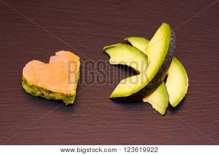 Slices of avocado and avocado and smoked salmon in a heart shape on top in slate