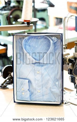 Handmade button down shirt in retail packaging displayed upright in a box in a tailors shop