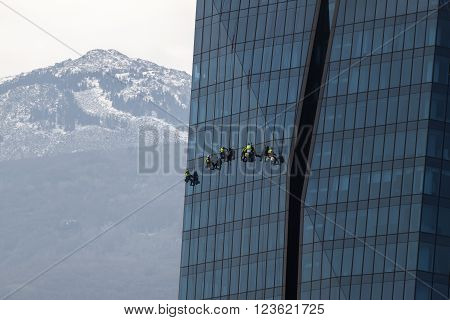 Six climbers wash windows and glass facade of the skyscraper on the background of mountains