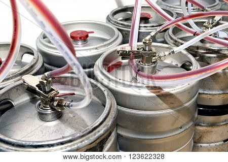 Metal drums filled with draught beer for a tavern or winery with pipes attached to a large cask or barrel with spigots for serving customers close view of the metal drums