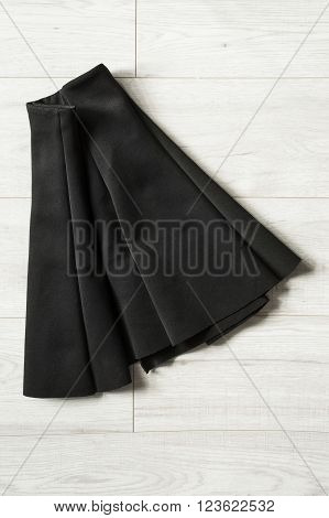 Black basics mini skirt folded on wooden background