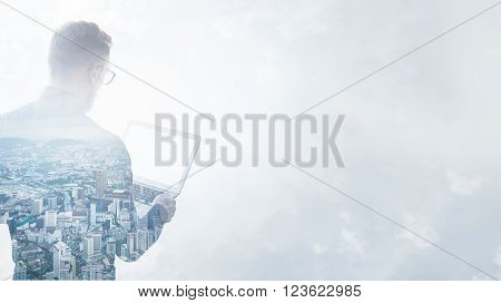 Double exposure  young bearded businessman wearing black shirt holding contemporary notebook hands.Isolated white, modern city background.Blank screen ready for your business message.
