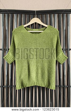 Khaki knitted pullover on clothes rack hanging on wooden screen