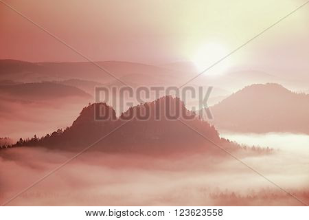 Fantastic dreamy daybreak above peaks of smoky mountain with the view into misty valley. Vivid and vignetting effect.