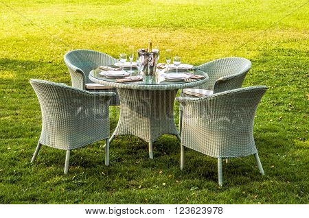 White rattan furniture table chairs and cushion outdoors in the garden
