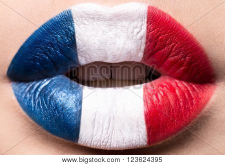 Female lips close up with a picture of the flag of France. Blue, white, red