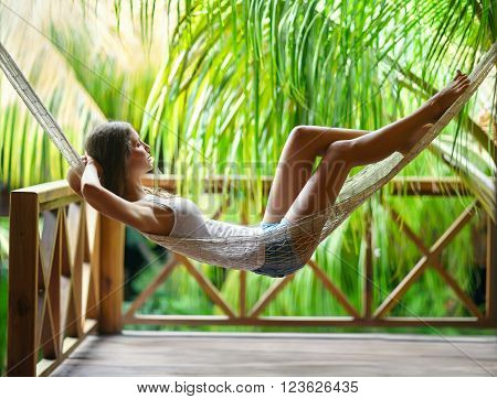 Young beautiful woman relaxing in hammock in a tropical resort