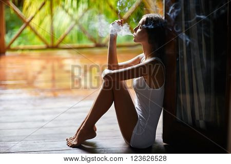 Sad lonely beautiful woman smoking cigarette and sitting on the porch during the rain