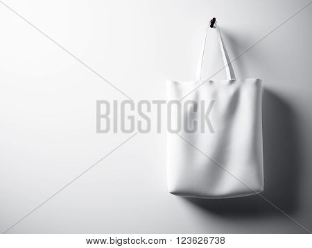 Photo white cotton textile bag hanging right side. Empty concrete wall  background. Highly detailed texture.