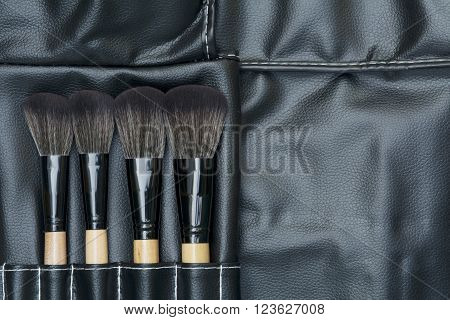 top view of makeup brushes on black leatherette background