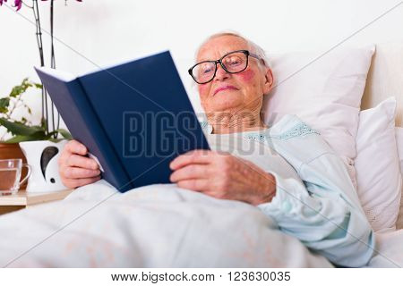 Elderly woman reading the Holy Bible in bed with smile on her face.