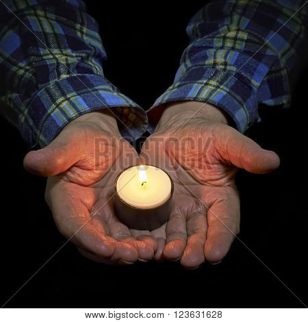 View of the old man hand holding a burning candle on a black background