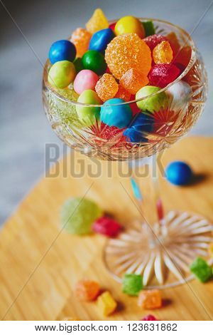 Colorful candies and jujube in vase on the wooden table