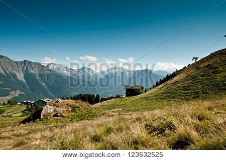 Idyllic landscape in the Alps with green meadows and snowcapped mountain tops in the background in summer day, Switzerland.
