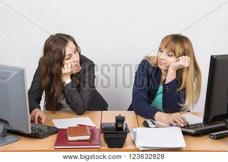 Two Young Office Employee Wearily Looking At Each Other Behind A Desk