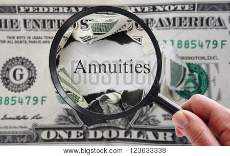 Hand holding a magnifying glass over torn dollar bill with Annuities text