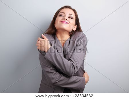 Happy business woman hugging herself with natural emotional enjoying face. Love concept of yourself.